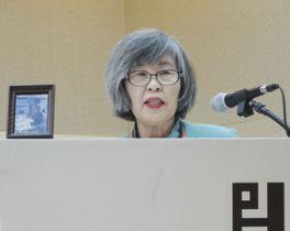 夫一正さんの遺影(左)を演壇に置き、犯罪被害者支援に携わる人たちが集まる国際会議でスピーチする高橋シズヱさん=25日、ソウル(共同)