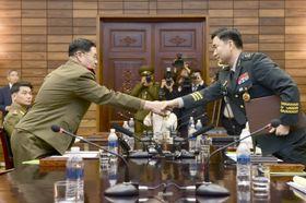 14日、板門店での南北将官級軍事会談を終え、握手する南北の首席代表(韓国国防省提供・共同)