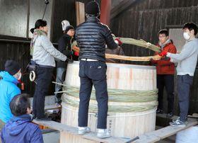 組み上げた木桶に「箍」をはめ込む参加者=小豆島町安田