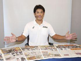 プレミア12の初優勝から一夜明け、新聞各紙を前にポーズをとる日本代表の稲葉監督=18日、東京都内のホテル