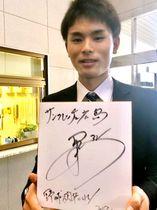 サッカーJリーグ・サンフレッチェ広島の松本泰志選手からの色紙を手に笑顔を見せる和田