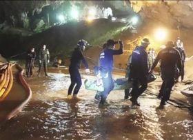 タイ北部チェンライの洞窟から助け出した少年を運ぶ救助隊員ら。タイ海軍特殊部隊が11日、フェイスブックで公開した(AP=共同)