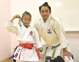 金メダルを手に恩師の喜友名諒選手(右)と笑顔を見せる島袋かなささん=6月23日、沖縄市体育館