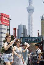 扇子で日差しを避けながら東京・浅草を歩く外国人観光客。奥は東京スカイツリー=7月