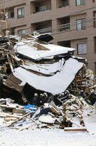 爆発と火災で倒壊した建物を現場検証する捜査員ら=19日午前10時55分、札幌市豊平区平岸