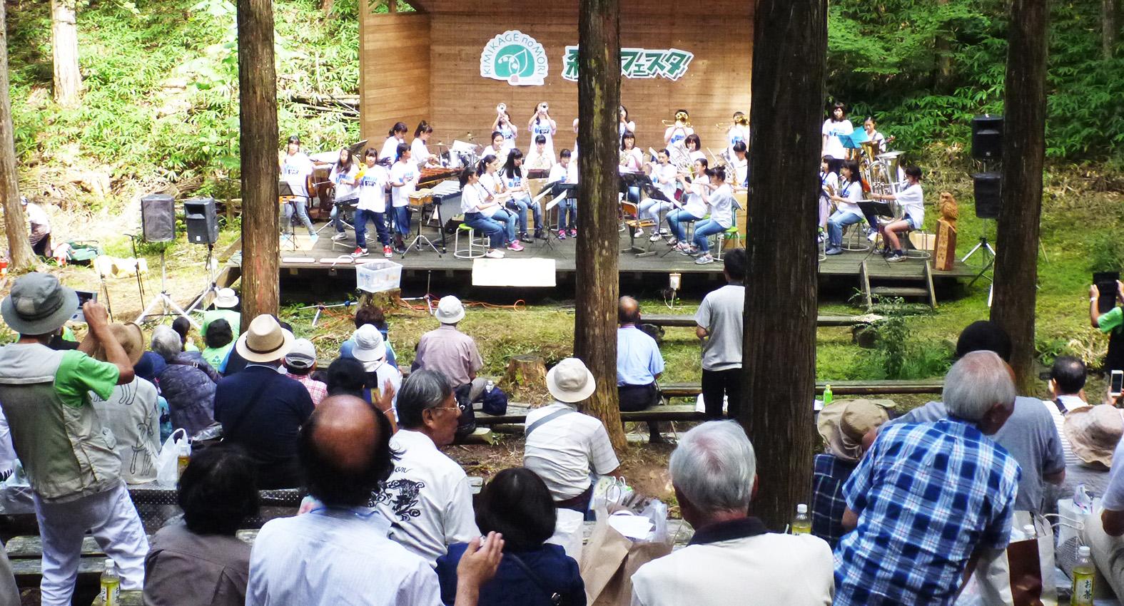 森の中に作ったステージで、さまざまな演奏が行われ、多くの人が集まった=2017年8月、奈良市(きみかげの森提供)
