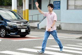 手を上げて横断歩道を渡る本紙記者。手を上げた場合、9割の車が止まった=12日、福島市泉