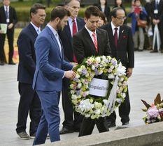 広島市の平和記念公園を訪れ、原爆慰霊碑に献花するMLBオールスターチームのミッチ・ハニガー外野手(手前左)と前田健太投手=12日午後