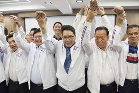24日、バンコクの党本部で記者会見後、ポーズをとる「国民国家の力党」のウッタマ代表(中央)や党幹部ら(共同)