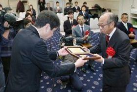 表彰される笠岡工高の牧野吉伸教諭(右)=ピュアリティまきび