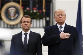 24日、米ホワイトハウスでの式典で、国歌の演奏を聞くトランプ大統領(右)とフランスのマクロン大統領(ロイター=共同)