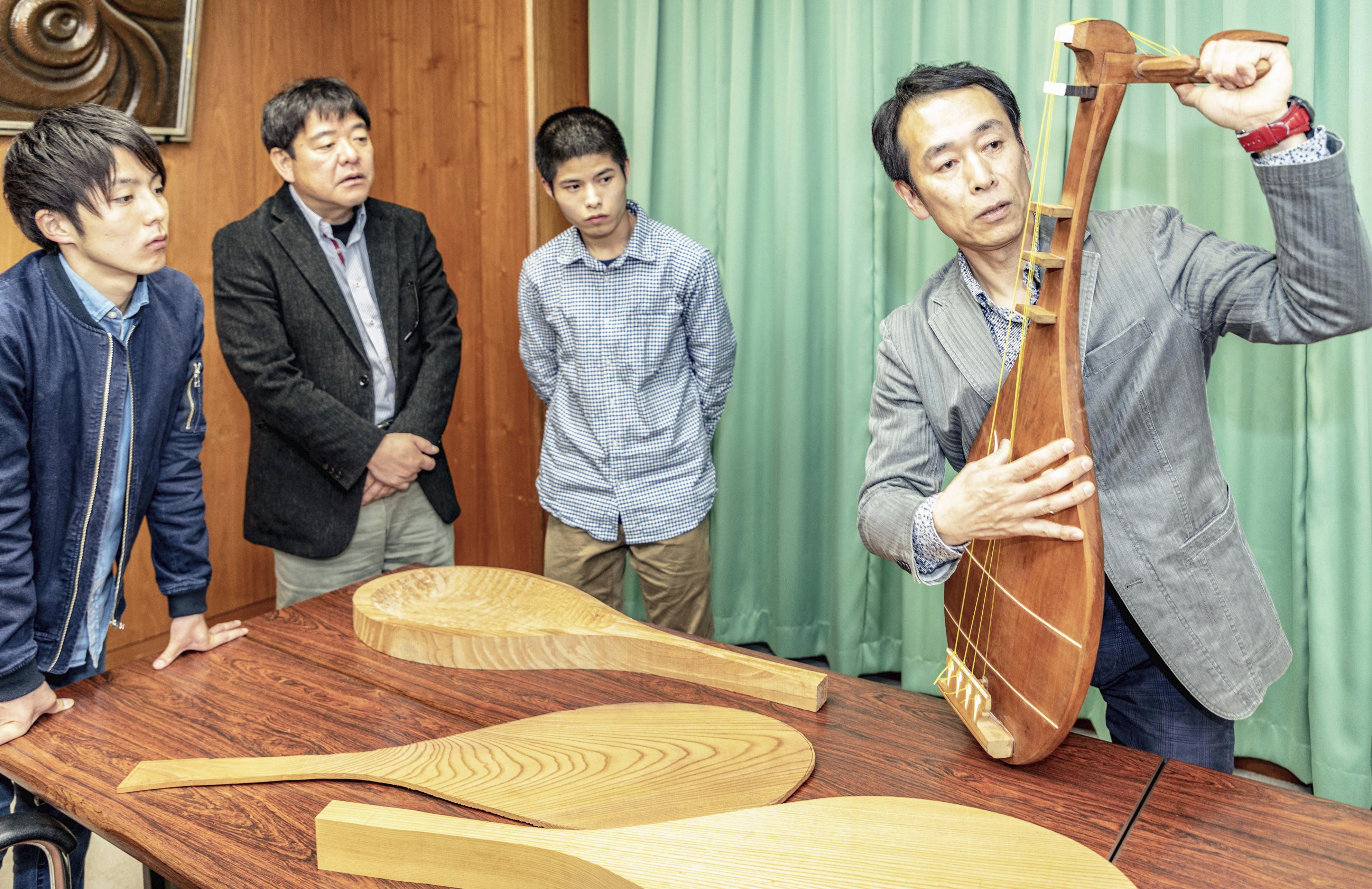 恵谷林太郎(中央右)が2年がかりで製作した琵琶を手に、指導する石田克佳。担当教授らも熱心に聞き入った=鹿児島市の鹿児島大
