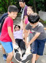 毛布を使った応急担架で負傷者を運ぶ練習をする子どもら=18日午後、松山市丸之内