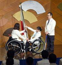 平昌冬季パラリンピックの日本選手団解団式で、大日方邦子団長(左)に団旗を手渡す村岡桃佳選手=19日夜、東京都内のホテル