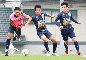 チームに合流し、ミニゲームで激しく競り合うMF松岡(中央)=鳥栖市北部グラウンド