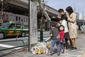 乗用車が暴走した事故現場で手を合わせる親子=20日午前8時50分、東京都豊島区