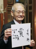 ノーベル賞の授賞式から一夜明け、サインを入れた色紙を手に持つ旭化成の吉野彰名誉フェロー=11日、ストックホルム(共同)