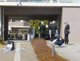 事件のあったマンションの階段付近を調べる警視庁の捜査員=17日午後、東京都多摩市