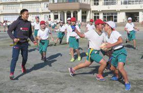 遠藤広太さん(左)も加わったラグビーの試合で、タックル代わりにタグを奪う児童=湖西市新居町で