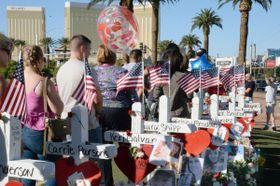 銃乱射事件で亡くなった犠牲者を悼み、目抜き通りに並んだ十字架。後方の右の建物は容疑者が銃を乱射したホテル=6日、米ラスベガス(共同)
