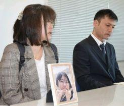 自殺した女子生徒の写真とともに記者会見に臨む両親=26日午後、熊本県庁