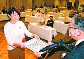 プランII部門でグランプリに輝いたTKY代表の政平さん(左)=徳島市の阿波観光ホテル
