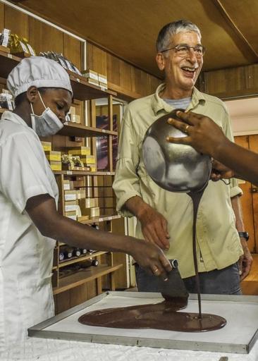サントメ島にあるチョコレート工房で従業員と笑顔のクラウディオ・コラロ(右)=3月(共同)