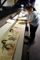 妖怪を描いた江戸時代の絵巻物を展示する学芸員