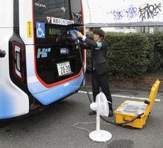 燃料電池バス「SORA」の後部からコードをつないで扇風機に電気を送る様子=25日午前、東京都港区
