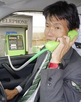 NTT西日本が設置した「ドライブスルー公衆電話」を利用する人。自動車に乗ったまま通話が可能=4月、愛知県日進市