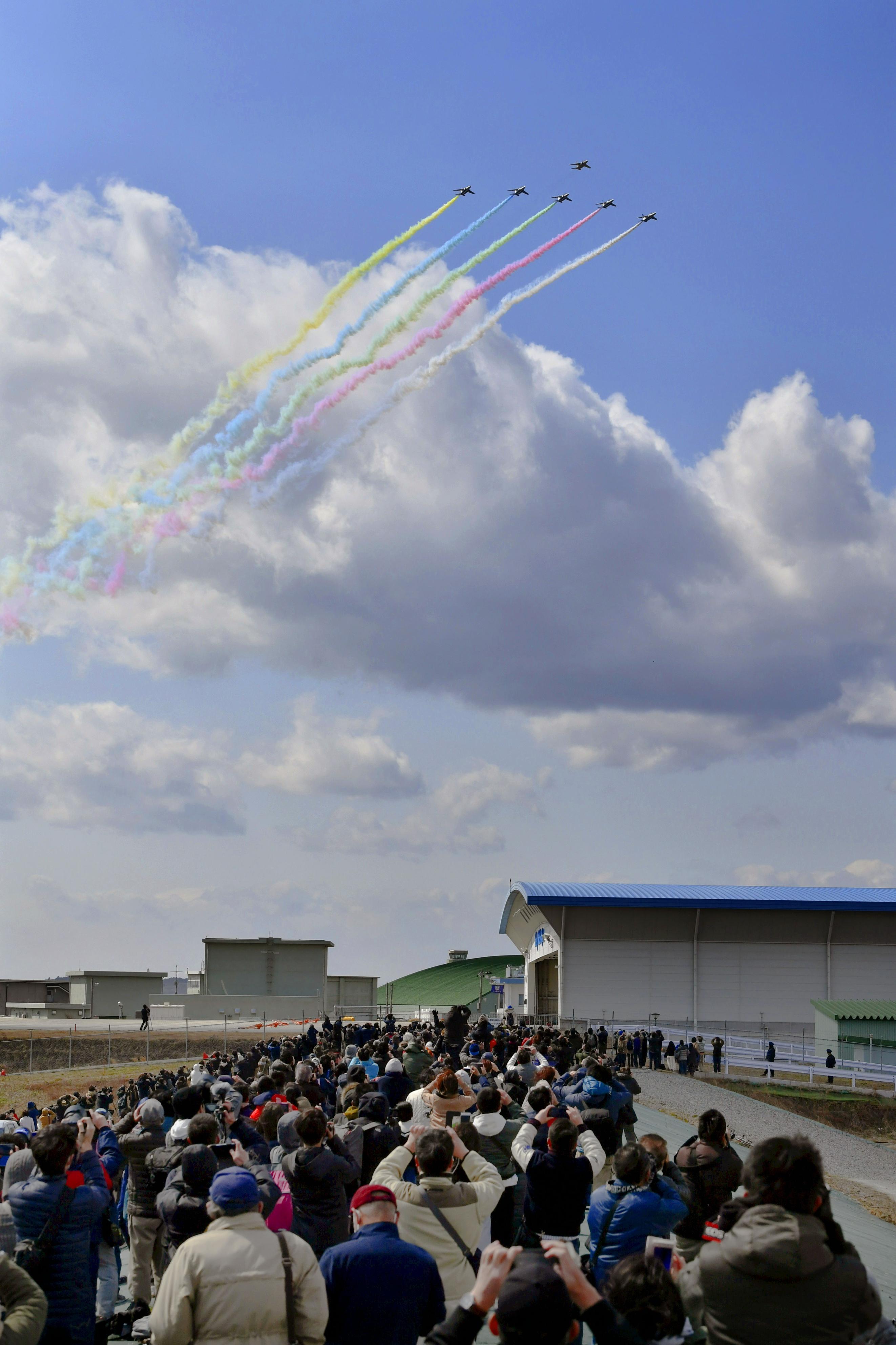 東京五輪の聖火到着を祝い、展示飛行する航空自衛隊「ブルーインパルス」=3月、宮城県東松島市