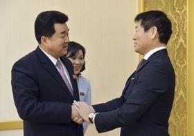 平壌で北朝鮮オリンピック委員会委員長の金日国体育相(左)と握手する国際体操連盟の渡辺守成会長=24日(共同)