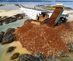 埋め立て区域に土砂を投入するダンプカー=14日午後、名護市辺野古