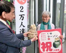 島谷館長(左)から入館2万人目の記念品を受け取る清田さん