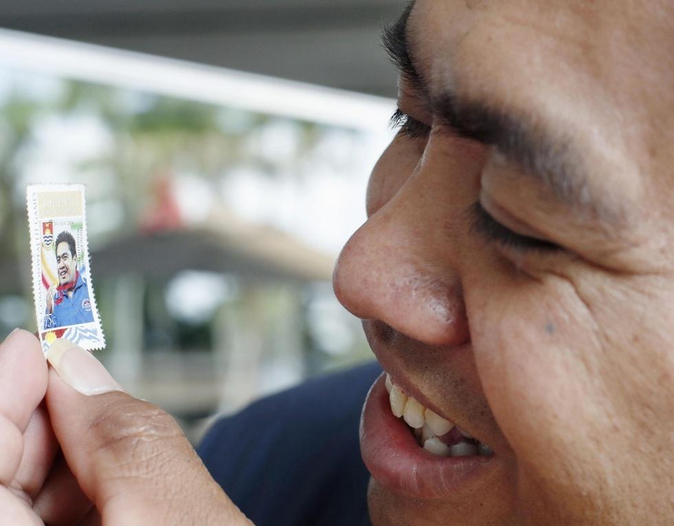 キリバスで使われている自身をデザインした切手を見て笑顔のデービッド・カトアタウ。財布に入れて持ち歩いている=マレーシア・ペナン島(撮影・大里直也、共同)