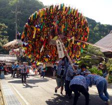 軸を傾けた状態で傘鉾を担ぎ、通りを駆け抜ける男衆