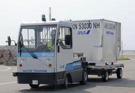 コンテナを引いて自動運転で走行するトーイングトラクター=26日午後、佐賀空港