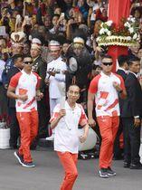 大統領宮殿の敷地内でアジア大会の聖火リレーをするインドネシアのジョコ大統領(手前)=17日、ジャカルタ(共同)
