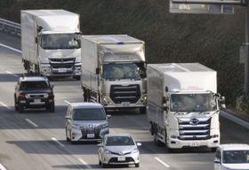 自動運転の実証実験で、新東名高速道路を隊列走行する3台のトラック=23日午後、浜松市