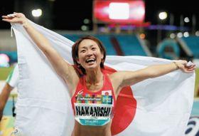 女子走り幅跳び(義足)で優勝し、日の丸を掲げ喜ぶ中西麻耶=ドバイ(ロイター=共同)
