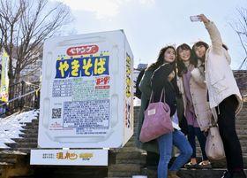 伊香保温泉の石段街に登場した「ペヤングソースやきそば」の巨大オブジェと記念撮影する大学生ら=1日、群馬県渋川市