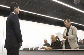 長崎県の平田研副知事(左)に石木ダム建設の断念を求める文書を読み上げる住民の岩下和雄さん=18日午前、長崎県庁
