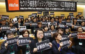 国会内で開かれた「セクハラ被害者バッシングを許さない」とする緊急集会で、「#WithYou」(「被害者に寄り添う」の意)と書かれたメッセージを掲げる参加者=23日午後
