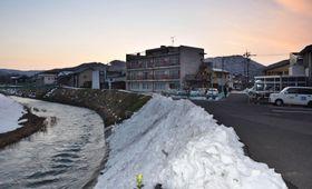 男児が行方不明になった駐車場(右)と近くを流れる川=19日夕、福井県越前市