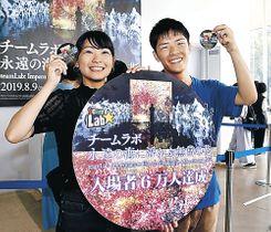 来場者6万人目となった島さん(右)と島田さん=金沢21世紀美術館