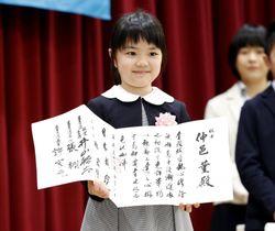 囲碁のプロ初段免状を手に笑顔を見せる仲邑菫さん。4月に史上最年少でプロ入りする=26日午後、東京都千代田区の日本棋院