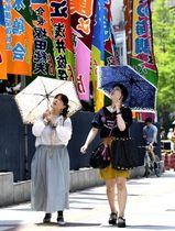 日傘を差して両国国技館前を歩く人たち=26日午前、東京都墨田区