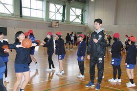 シュートの打ち方を指導する鈴木豊選手(右手前)=金沢市額小で