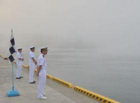 濃霧に覆われた出崎埠頭で、護衛船を待つ自衛隊員ら=20日、宮古市臨港通