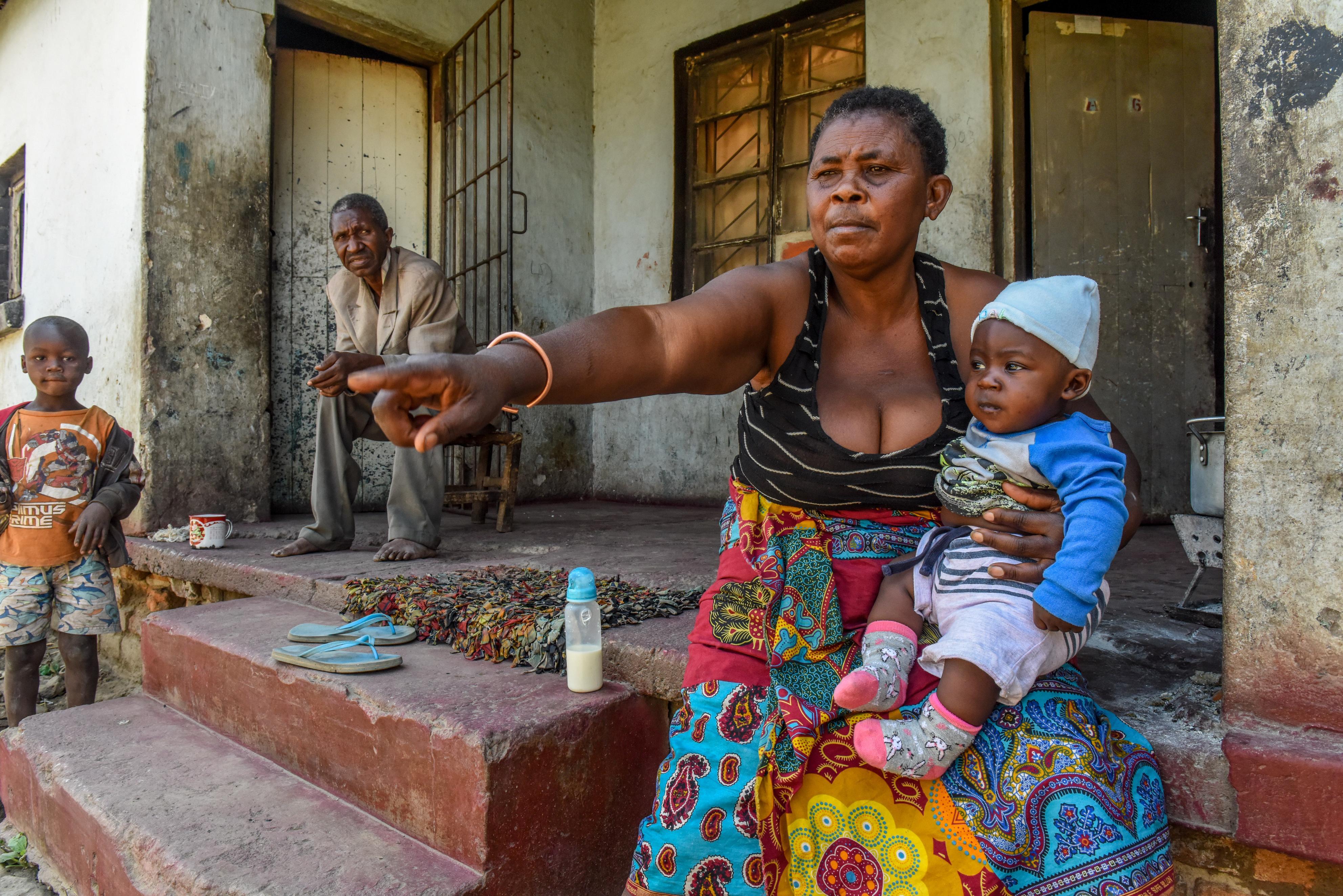 生まれたばかりの孫をひざに「すぐそこの土地が鉛で汚染されている」と指さすマリー。夫バリー・ナヒール(奥)は孫たちへの影響が気にかかると訴えた=8月、ザンビア・カブウェ(共同)